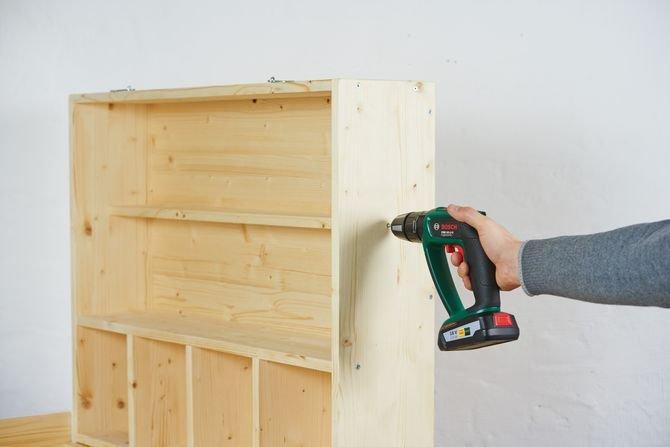 Przykręć ramę półki do tyłu przewijaka, po czym złóż wewnętrzną cześć półki i przymocuj ją do ramy i tylnej ściany.