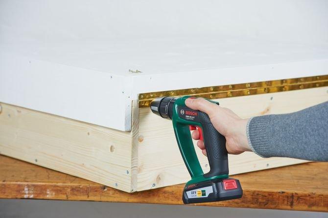 Jeżeli chcesz zaoszczędzić miejsce zastosuj mechanizm, który umożliwi złożenie przewijaka. Przykręć zawias taśmowy do bazy i tylnej półki za pomocą krótkich śrub do drewna. Pomoże w tym akumulatorowa wiertarko-wkrętarka z udarem Bosch PSB 18 LI-2.