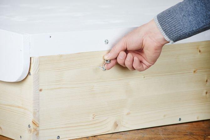 Na szczycie półki przymocuj dwa haczyki do zamykania przewijaka, a oczka na zewnętrznej stronie przewijaka. W ten sposób składana cześć będzie się mocno trzymać tyłu przewijaka po zamknięciu.