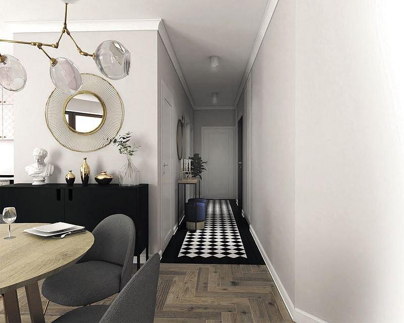 Na podłodze w połączonym z kuchnio-jadalnią przedpokoju położono biało-czarną szachownicę z płytek ceramicznych. To bardzo mocny element wystroju, który decyduje o charakterze tego pomieszczenia. Tu również pojawiają się złote detale. W takiej barwie jes.