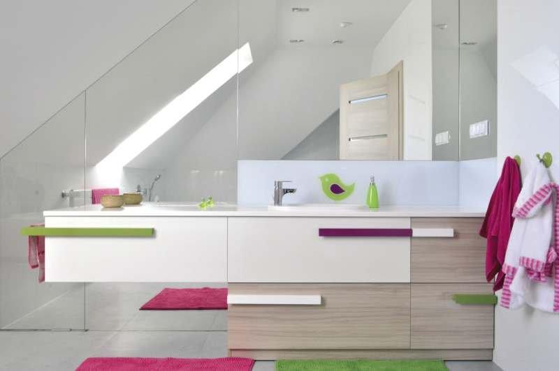 W dziecięcej łazience ściana wykonana z luster optycznie wydłuży wnętrze, a zastosowanie białych ścian i dopływ naturalnego światła przez okno dachowe dodatkowo je powiększy.