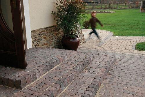 Schody tarasowe z kostki brukowej naturalnie wprowadzają w ogrodowe ścieżki