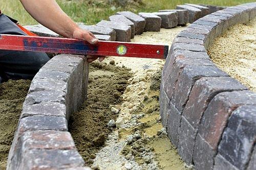Ważny etap prac to dokładne pomiary. Podczas układania elementów brzegowych wykonawca nie rozstaje się z poziomicą i metrówką.