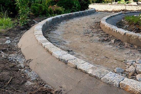 Ścieżka ogrodowa wymaga prawidłowego obramowania. Można wykorzystać do tego elementy brzegowe lub – jak na zdjęciu, np. stabilnie osadzoną kostkę granitową.