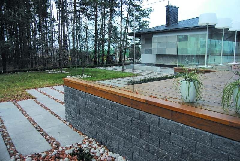 Betonowy murek oraz oryginalna w formie donica z betonowych elementów współgrają z architekturą budynków i wpisują się w otoczenie