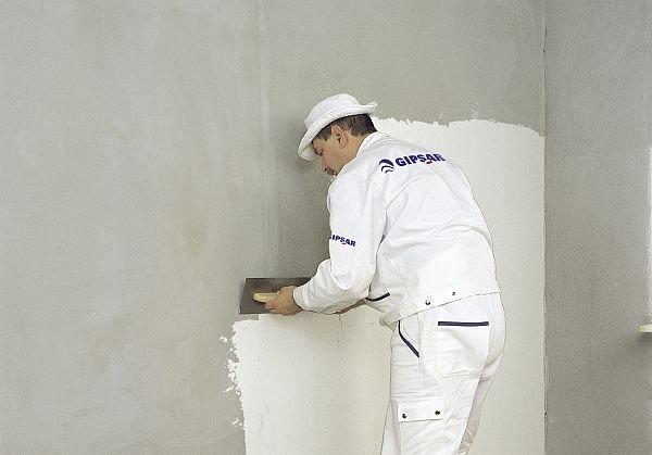 ...oraz ściany, przesuwając pacę od podłogi ku górze ściany
