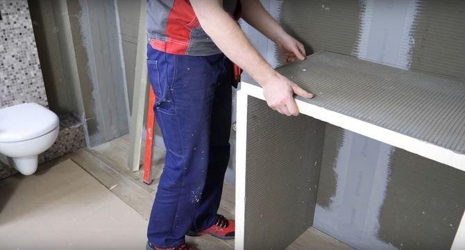Montaż zabudowy dla pralki zacznij od stworzenia podparcia dla blatu. Przed klejeniem upewnij się, że pomiędzy płytą a ścianą zachowany jest kąt 90°. Następnie nałóż na podłogę klej z uszczelniaczem i nasuń płyty, które będą pełnić rolę nóżek.