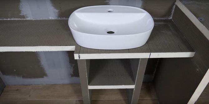 Stworzenie zabudowy pod umywalkę przebiega analogicznie do zabudowy pralki. Po przyklejeniu wyciętych z płyt nóg i połączeniu ich z blatem zostaje przestrzeń pod zlewem, którą możesz  wykorzystać na dodatkową półkę.