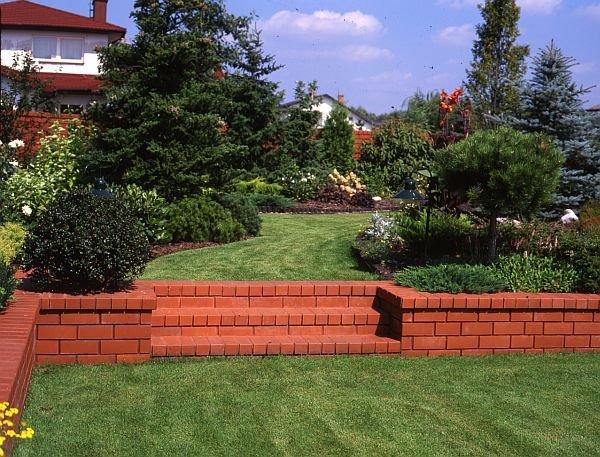 Różnice poziomu wyznacza murek oporowy z cegły klinkierowej. Kolor cegły dobrze komponuje się z zielenią.