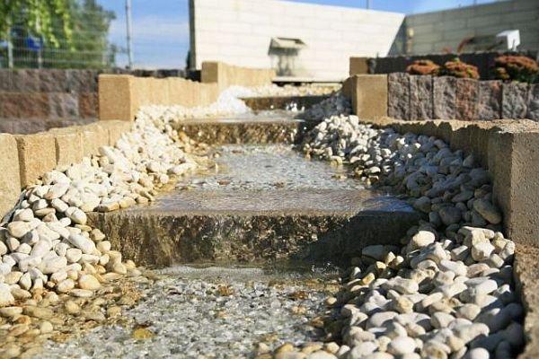 Palisady i płyty schodowe (Libet Completto) oraz kamień i grys ozdobny (Libet Patio) wystarczą do wytyczenia koryta strumienia.