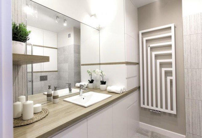 Obszerna szafka pod umywalką, a obok niej sięgający sufitu słupek na pralkę, kosz na bieliznę i środki do prania. Wszystko więc można schować, a na wierzchu pozostawić tylko estetyczne przedmioty.Fot. MGN Pracownia Architektoniczna