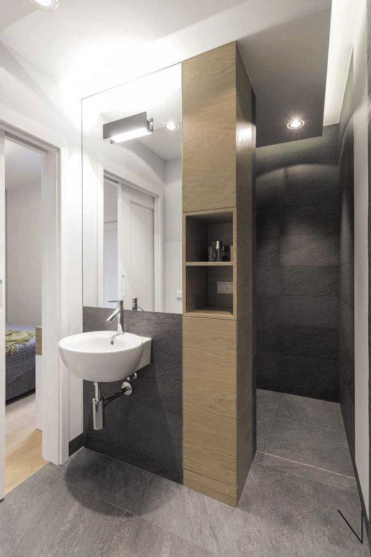 Przy wejściu do kabiny prysznicowej postawiono wysoki słupek, który całkowicie rozwiązał problem przechowywania w tym niewielkim pomieszczeniu.