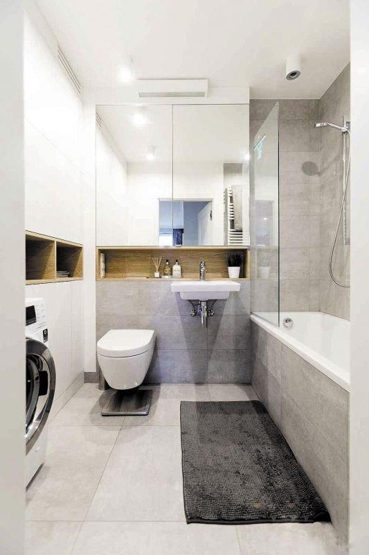 Nad umywalką i WC zamontowana została wysoka szafka z lustrzanymi drzwiczkami, a przy ścianie obok pojemna zabudowa od podłogi do sufitu. Ponieważ w pomieszczeniu nie zmieściłaby się szafa o głębokości 70 cm, zdecydowano się na płytszą. Nie udało się wię.