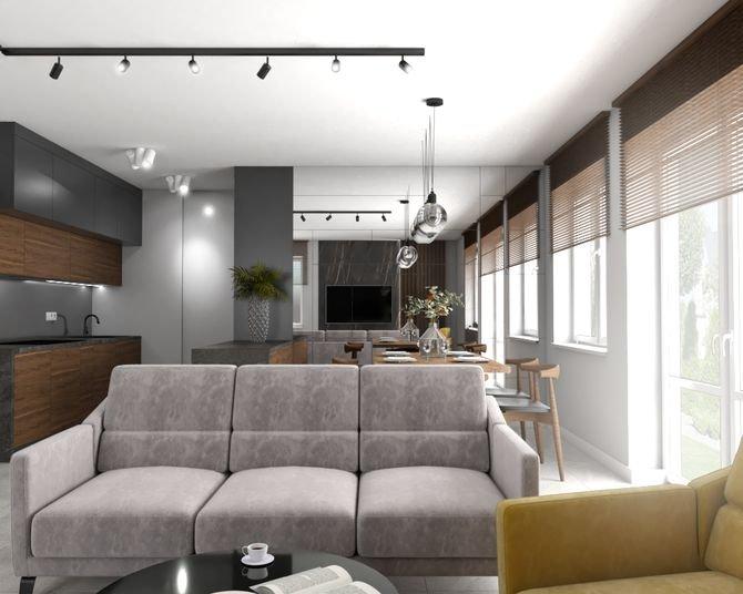 Zabudowa kuchenna z trzech rodzajów płyt: fornirowanej drewnem orzecha, lakierowanej na szaro i na biało, ma salonowy charakter, dzięki czemu idealnie komponuje się z resztą wystroju otwartej strefy dziennej. W lustrze, którym wyłożono ścianę za jadalnią.
