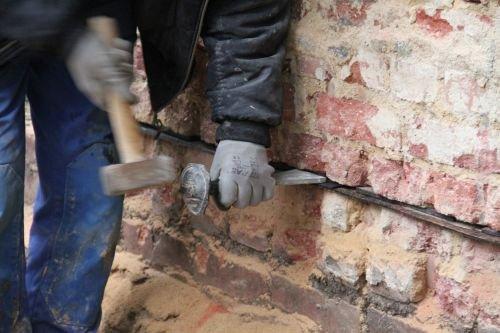 Zdj. 4. Wbijanie klinów zapobiegających osiadaniu ścian