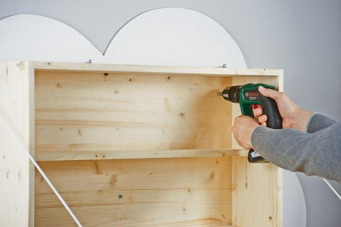 Przymocuj przewijak oraz chmurę do ściany przy użyciu pięciu kołków do ścian i śrub rozmieszczając je w równych odstępach. Przymocuj dwie śruby z oczkami do ściany po lewej i prawej stronie górnej części przewijaka