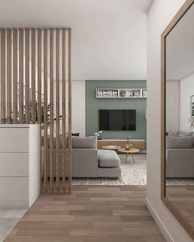 Przepierzenie z dębowych listew oddziela salon od przedpokoju. Ażurowa konstrukcja przesłania obydwie części pomieszczenia oraz to, co w nich się dzieje, ale nie ogranicza przy tym przestrzeni jak pełna ściana.