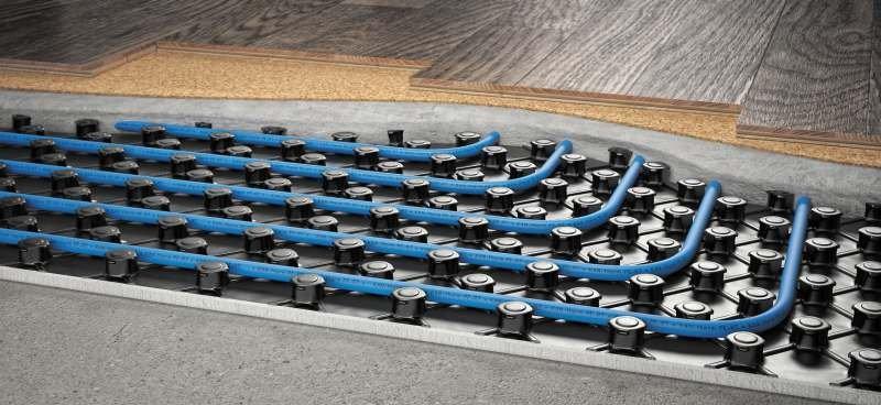 Sposób mocowania rur ogrzewania podłogowego do izolacji termicznej poprzez wciśnięcie pomiędzy specjalne wypustki w izolacji; fot. KAN