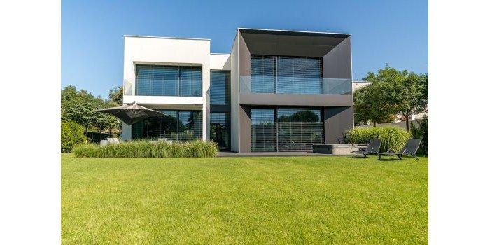 Fot. 1. Gra szkłem gra w nowoczesnych projektach domów pozwala na osiągnięcie niesamowitego, indywidualnego efektu. Aluminiowe okna FEN 86 A od KRISPOL świetnie prezentują się z modnymi żaluzjami fasadowymi.